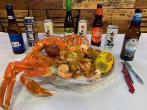 Seafood Boil Bag with Crab Legs, Corn, Potatoes, Shrimp and Lime. On table with Beer and Wine samples with crab pliers.