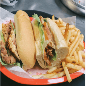 Po' Boy with tomato and lettuce with a side of Fries.